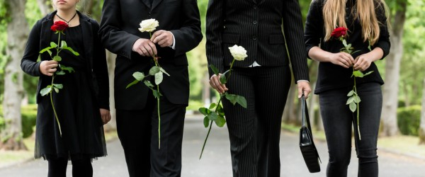 People in Black carrying flowers